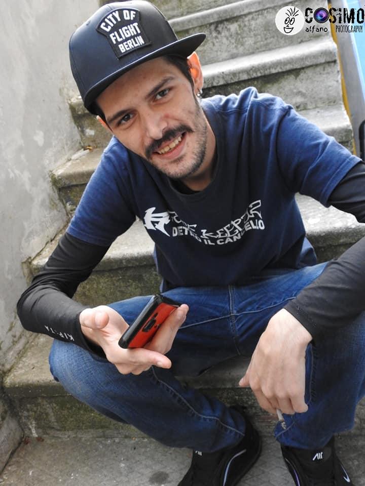JO Vezz seduto su dei gradini con berretto e telefonino in mano
