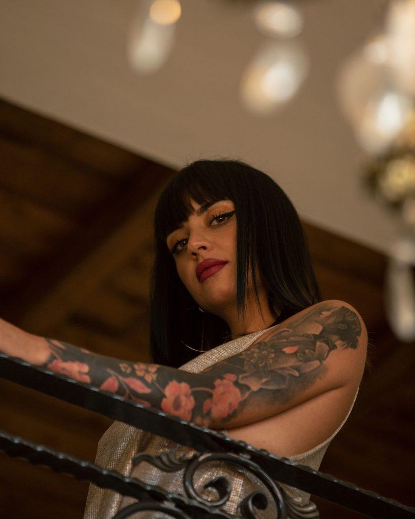 mis7ica baila - nella foro la rapper che guarda l'obiettivo di sbieco, il braccio sinistro coperto di tatuaggi
