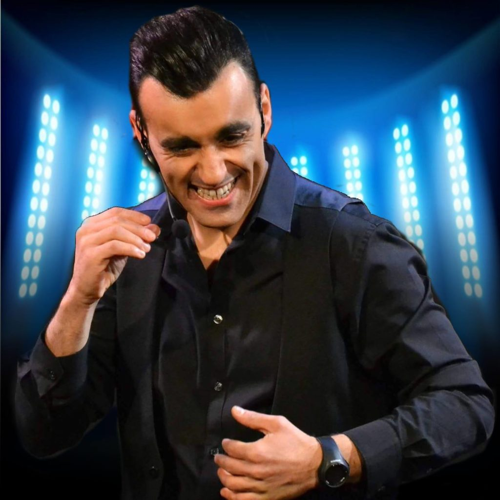 Manuel Negro con camicia nera, microfono che ride di gusto