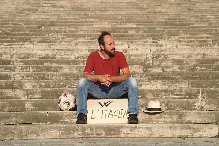 mauto fotografato su una scalinata, indossa jeans e maglietta rossa, con ai piedi il lartello con scritto viva l'itaglia