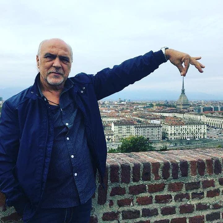 #CabaretShow - Pippo Romano con sullo sfondo la città di Torino lui tiene tra le dita la punta della Mole Antonelliana
