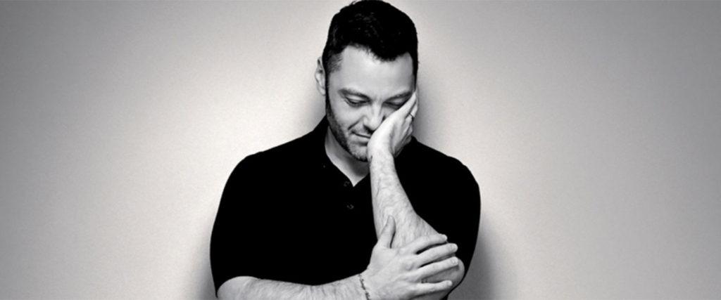 rimmel tiziano ferro - nella foto in bianco e neroo il cantante con il viso appoggiato alla mano sinistra, vestito di nero