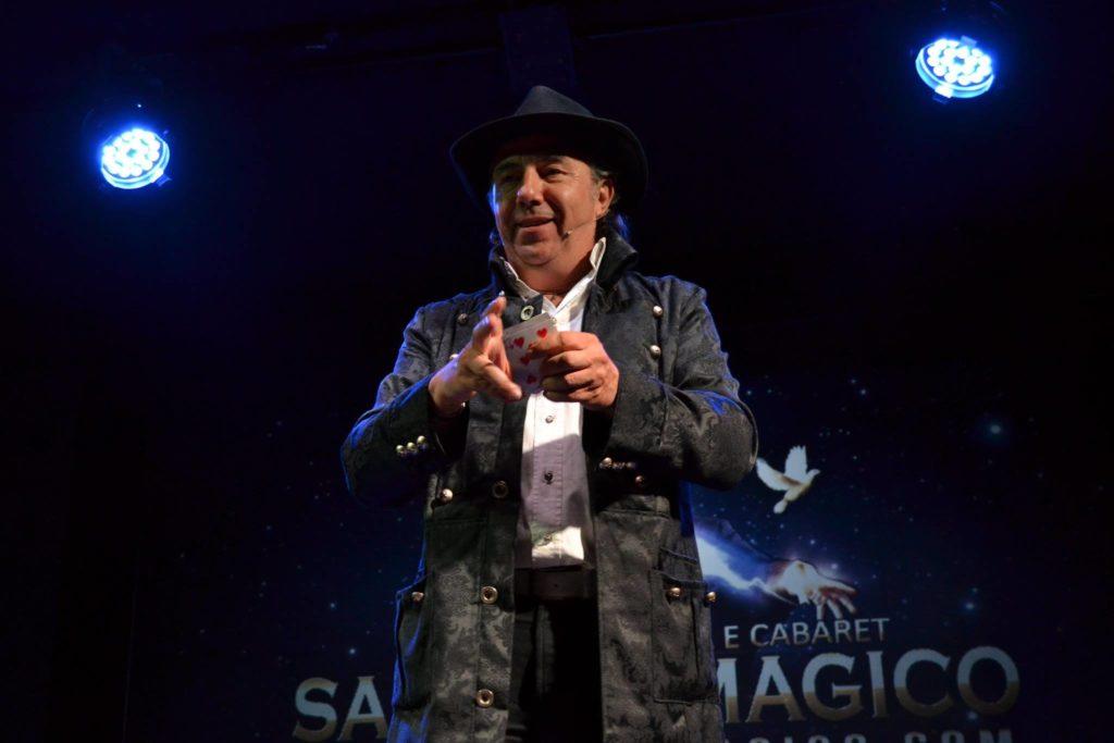#CabaretShow - Walter Perino con cappello e giacca con un mazzo di carte in mano durante uno spettacolo di magia