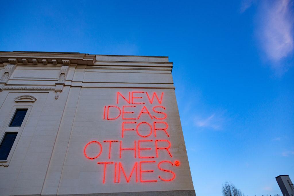 """Un edificio con la scritta rossa """"New ideas for other times"""""""