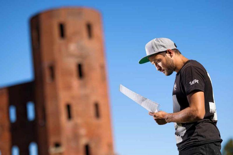 """Saype , l'artista che affresca l'erba, e il suo """"abbraccio"""" a Torino alle Porte Palatine. artista con cappellino davanti a i muri"""