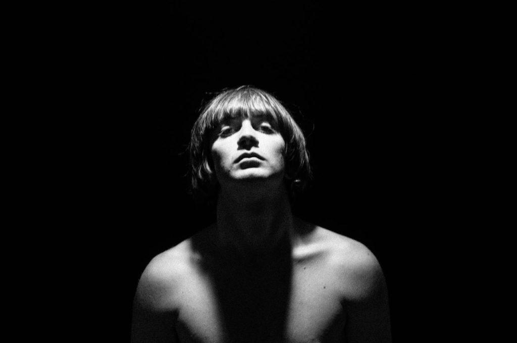 la paura di matteo alieno - primo piano in bianco e nero del giovane cantautore romano, a torso nudo e i capelli a caschetto
