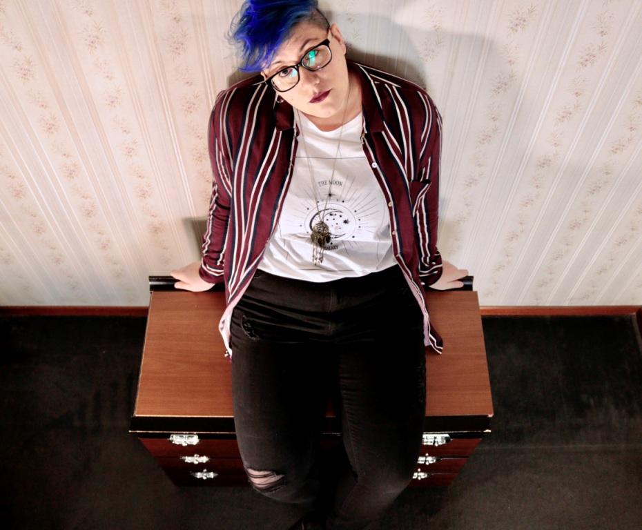frances aravel - inquadratura dall'alto della cantante, capelli tinti di blu, occhiali da vista dalla montatura nera, seduta su un cassettone