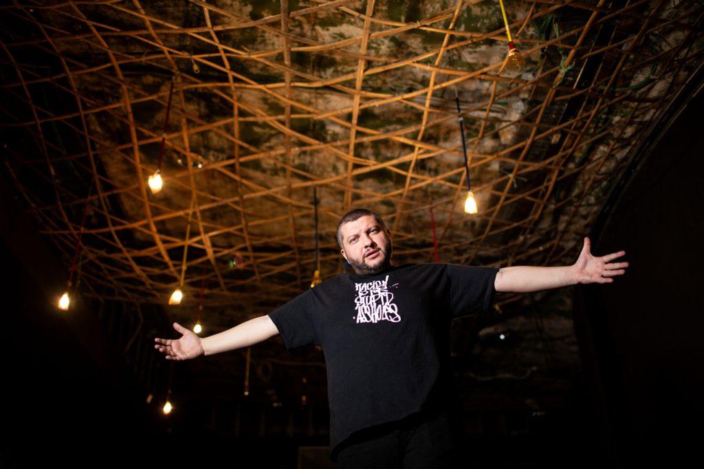 cinque anarchici - kento feat mad simon - nella foto il rapper calabrese, a braccia aperte, che indossa una t-shirt nera