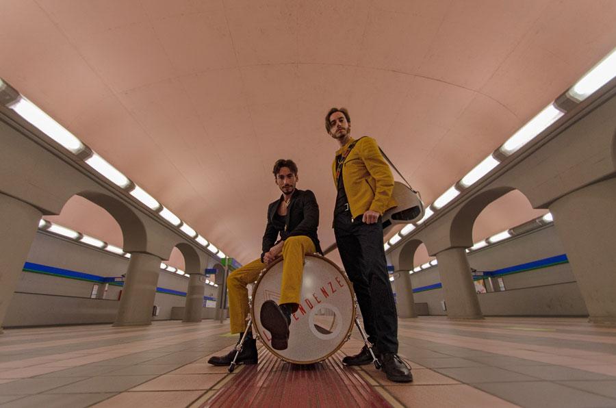 bugiardo happy birthday - le tendenze - nella foto i due musicisti abbigliati di nero e giallo: uno in piedi, l'altro seduto sulla grancassa di una batteria