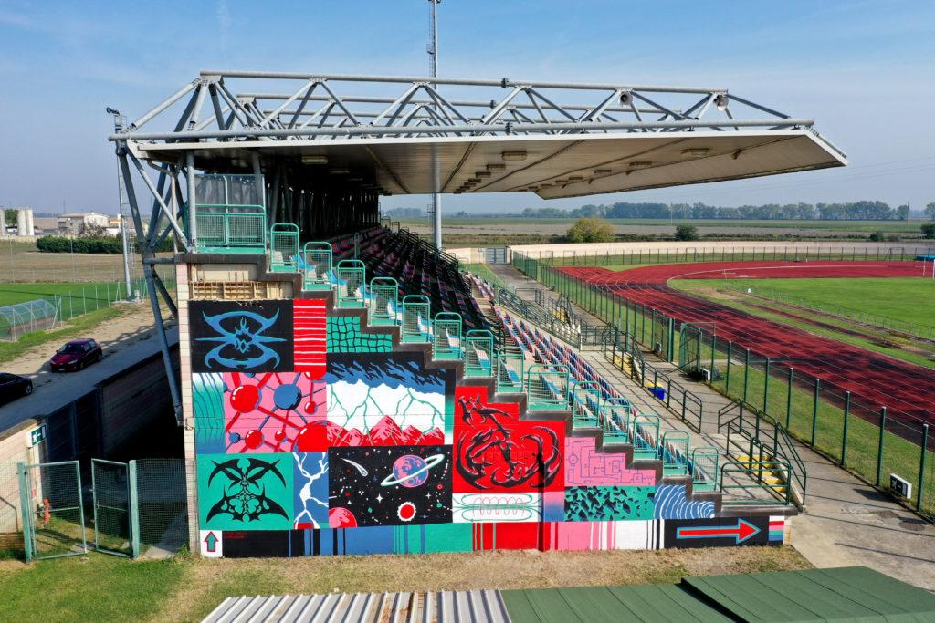 Stadio di Comacchio - la parete delle gradinate colorata con disegni di street art