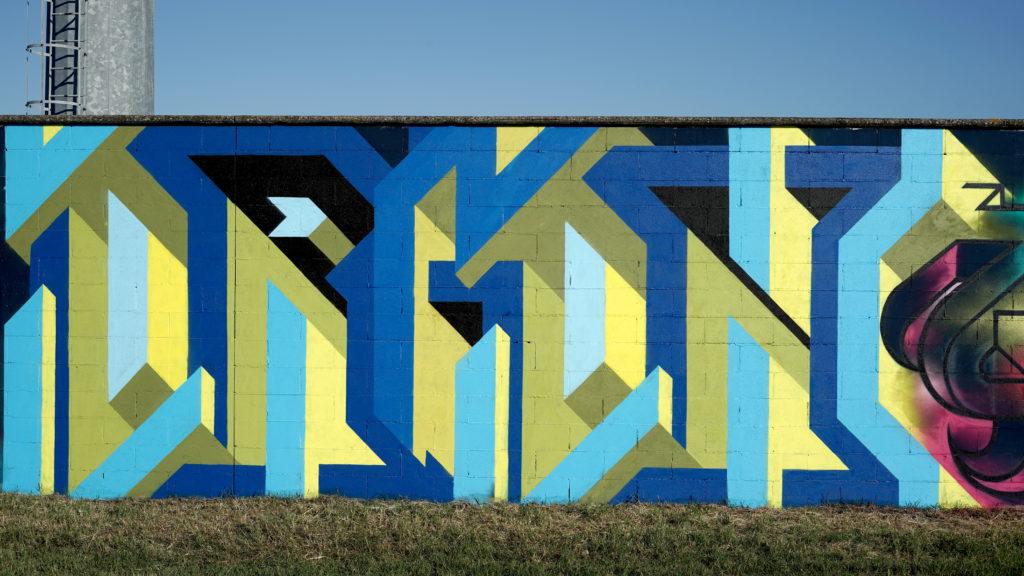 Manufactory Prject - un murales scritta in blu e giallo