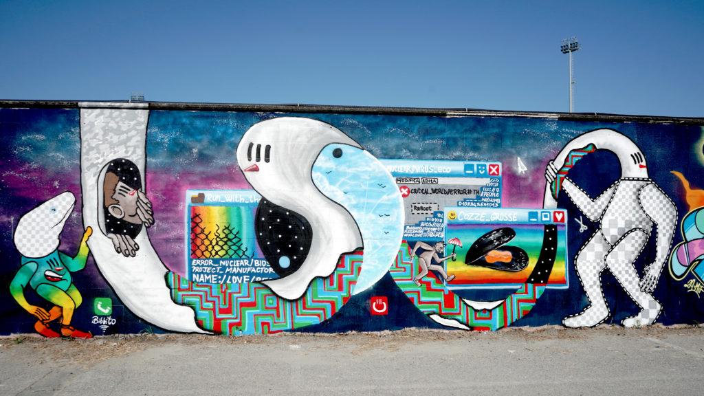 Stadio di Comacchio - un murales disegnato da street artist rappresentante delle finestre di windows, in mezzo a una balena, un mostro marino e