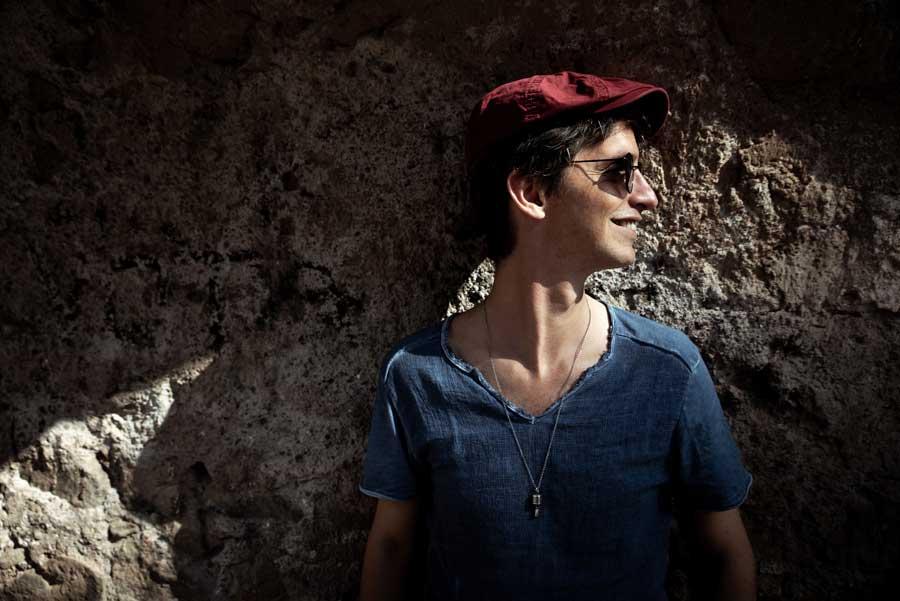 vasco barbieri - il cantautore, cappello rosso e occhiali da sole, che indossa una t-shirt azzurra, appoggiato ad uno scoglio