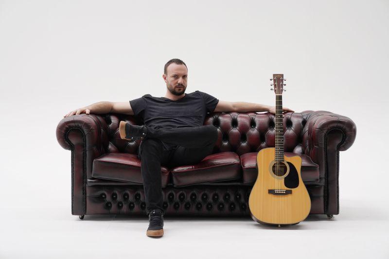 antonio carluccio la parola - il cantautore seduto a gambe accavallate su un divano di pelle marrone, di fianco una chitarra acustica