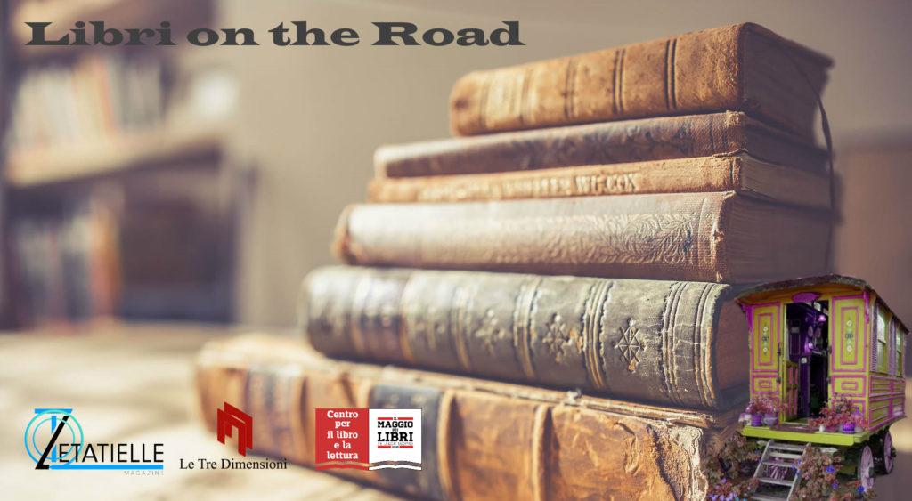 quando l'arte incontra la lettura - la locandina di libri on the road con dei libri appoggiati uno sull'altro e un carrozzone tipo antica roulotte appoggiato sulla destra