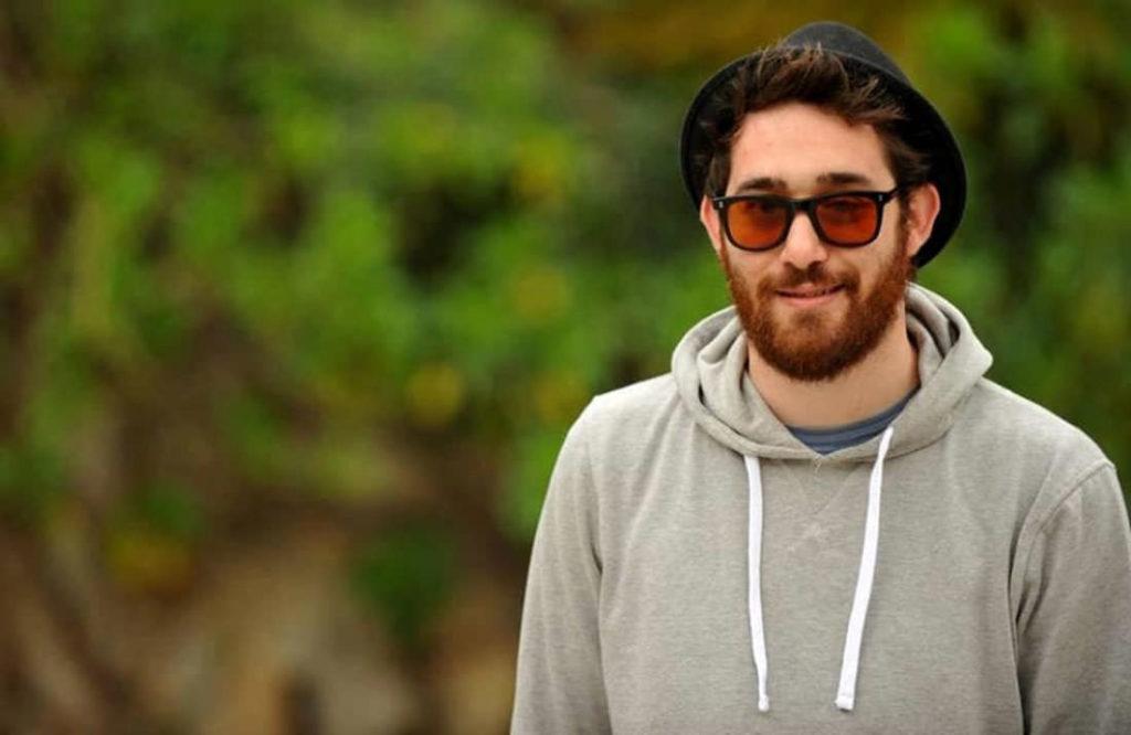 Maldestro egosistema nuovo album - l'artista con felpa grigia con cappuccio, barba, occhiali da sole e cappaello