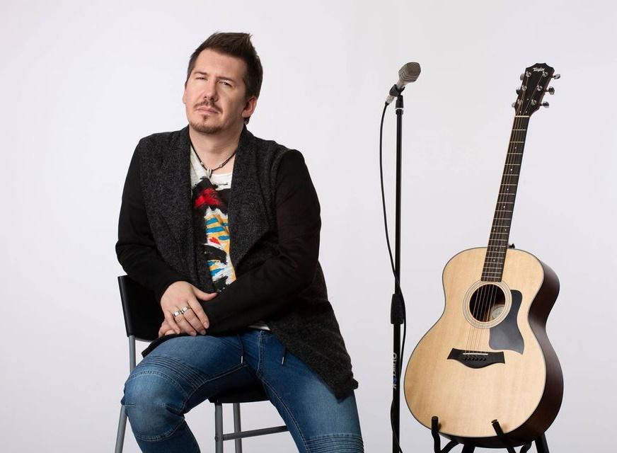 andrea rana - il cantautore, seduto su uno sgabello, giacca nera e jeans blu, di fianco l'asta di un microfono e una chitarra acustica