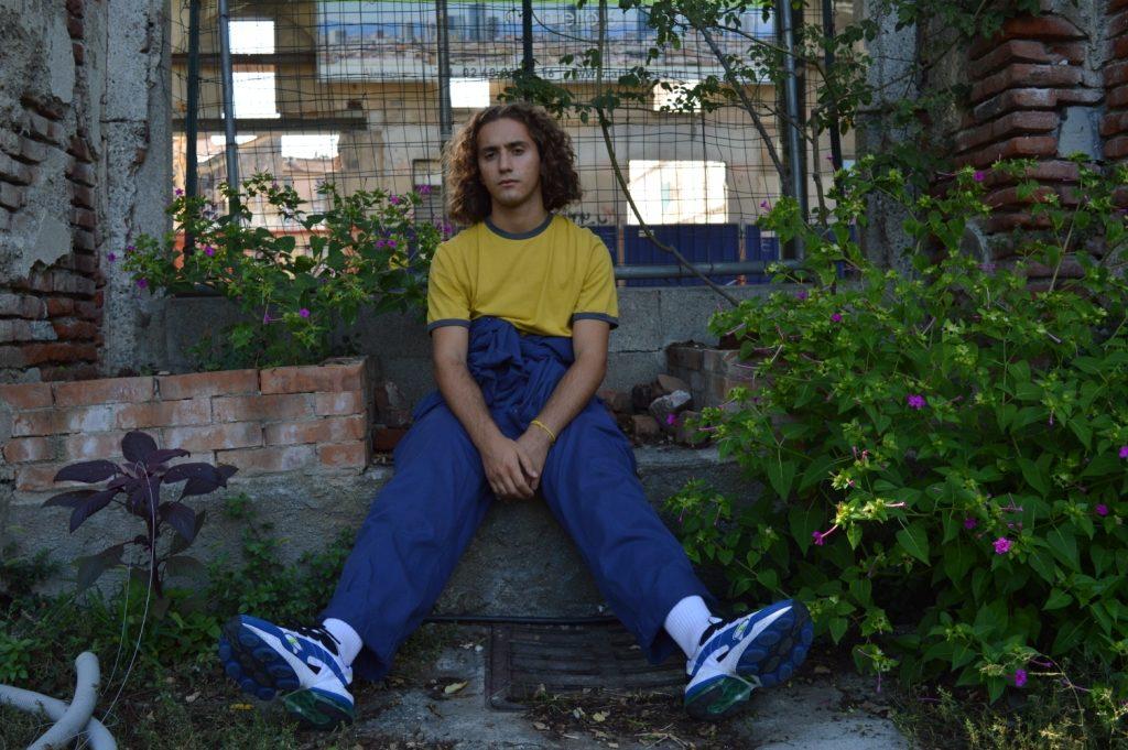 carme time - il cantante seduto su una panchina in mezzoalle piante, che indossa jeans blu e maglietta gialla