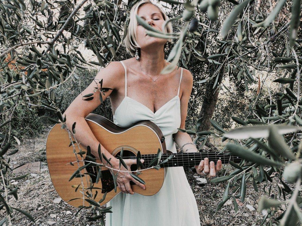 chiara ragnini la sera è ormai notte - La bionda cantante ligure, chitarra a tracolla, indossa un vestito bianco davanti ad un albero d'ulivo