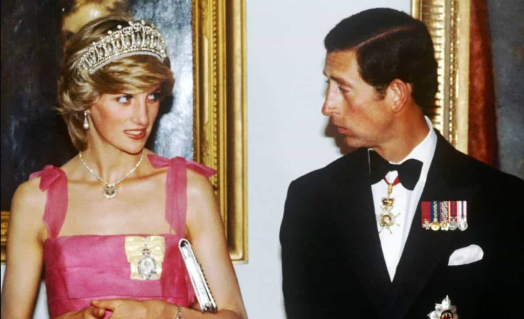 serie tv netflix - carlo e diana veatiti da sera, lei con un abito rosa conspalline e lui con smoking nero e medaglie al petto