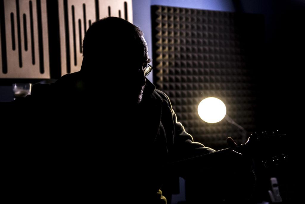 pietre giors - il cantautere torinese, in controluce, in uno studio di regisrazione, mentre suona la chitarra