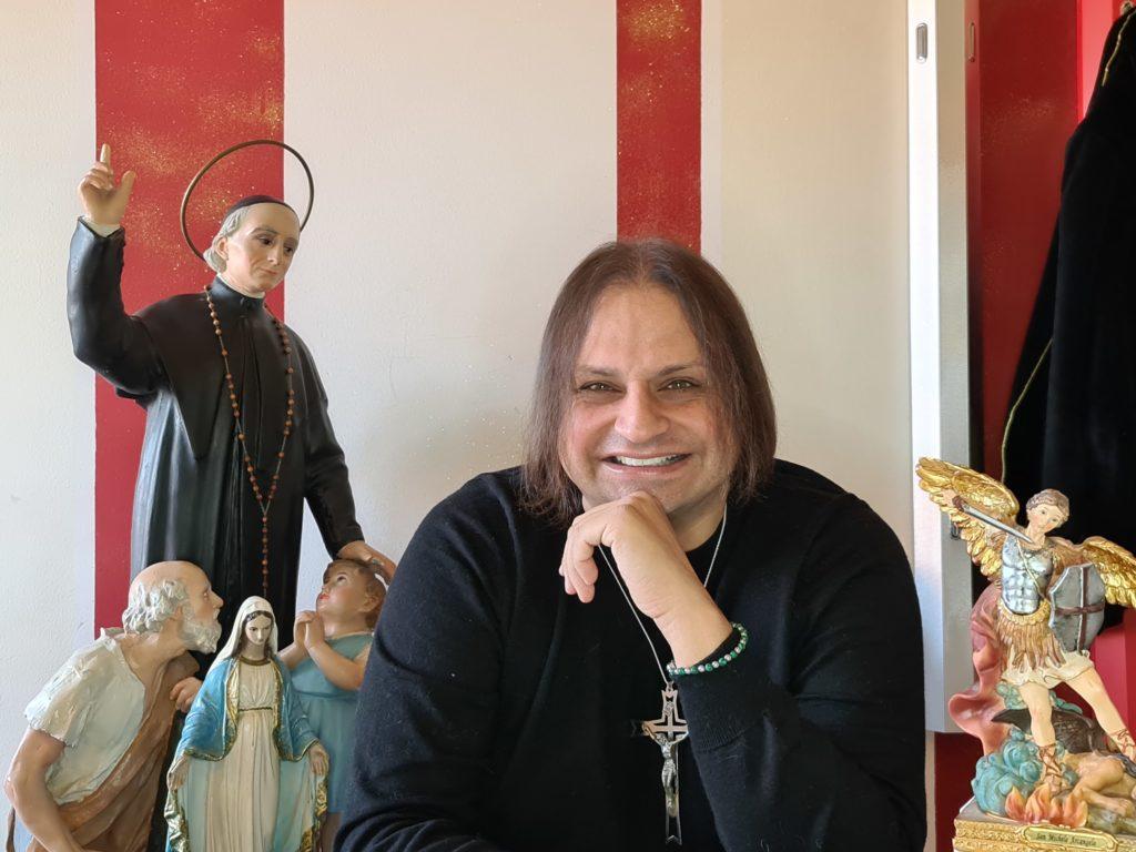Maurizio Scandurra sorridente e sullo sfondo le statue della Sacra Famiglia, San michele e Don Bosco