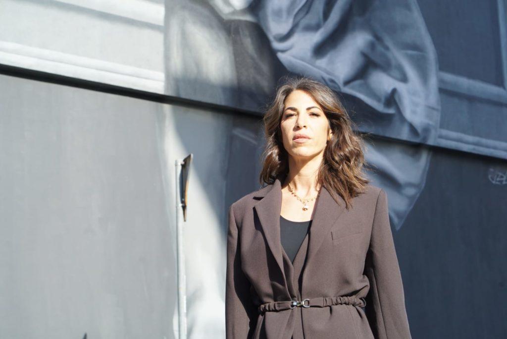 LGBT - Veronica dE Angelis con tailleur beige, lunghi capelli castani, vicino all'opera Outside In
