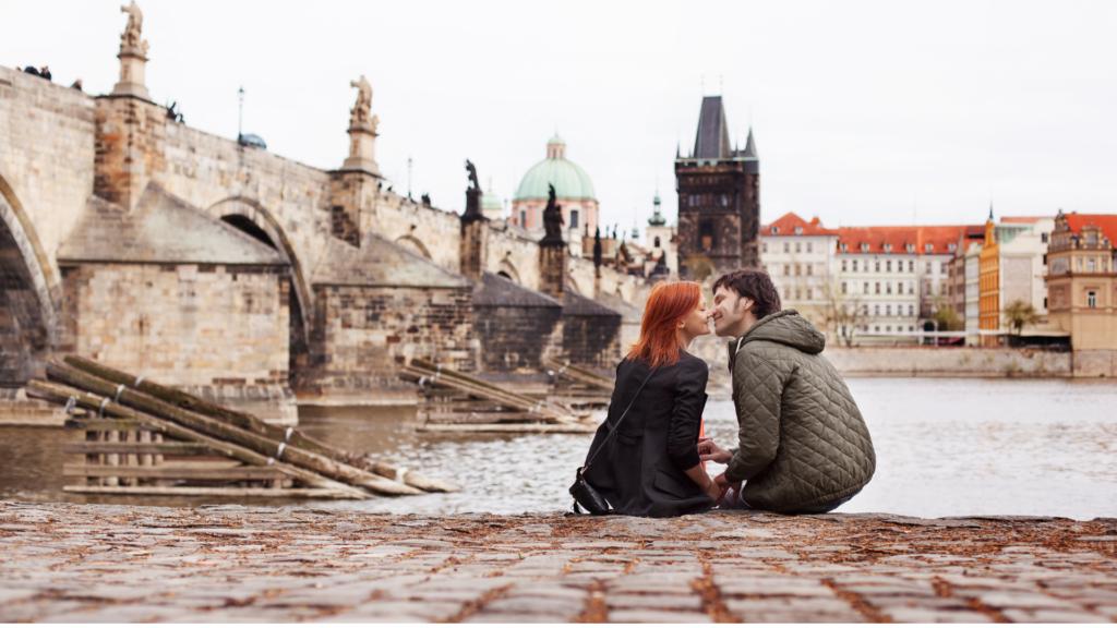 Una coppia di fidanzati si baciano lungo la banchina del fiume Moldava.