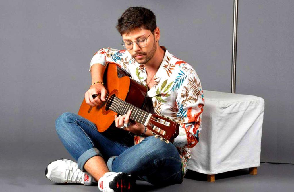 niccolò battisti seduto a gambe incrociate, jeans e camicia colorata, intento a suonare la chitarra