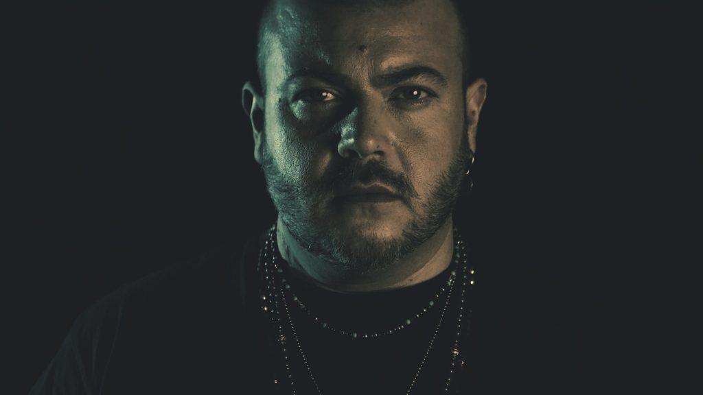 antonio marino in un frame del videoclip - sfondo scuro, e primo piano che evidenzia la t-shirt nera, le collane