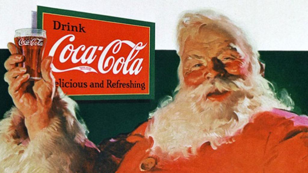 """Curiosità riti e usanze di Natale - nella foto Babbo Natale vestito di rosso, con la barba bianca lunga, tiene in mano un bicchiere di coca cola e dietro di lui il pannello pubblicitario con la scritta """"Coca Cola"""""""