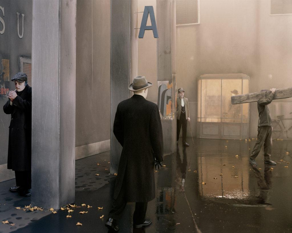 uno scorcio di un padiglione di una stazione degli autobus con dei pilastri e degli uomini vestiti con abiti degli anni 30