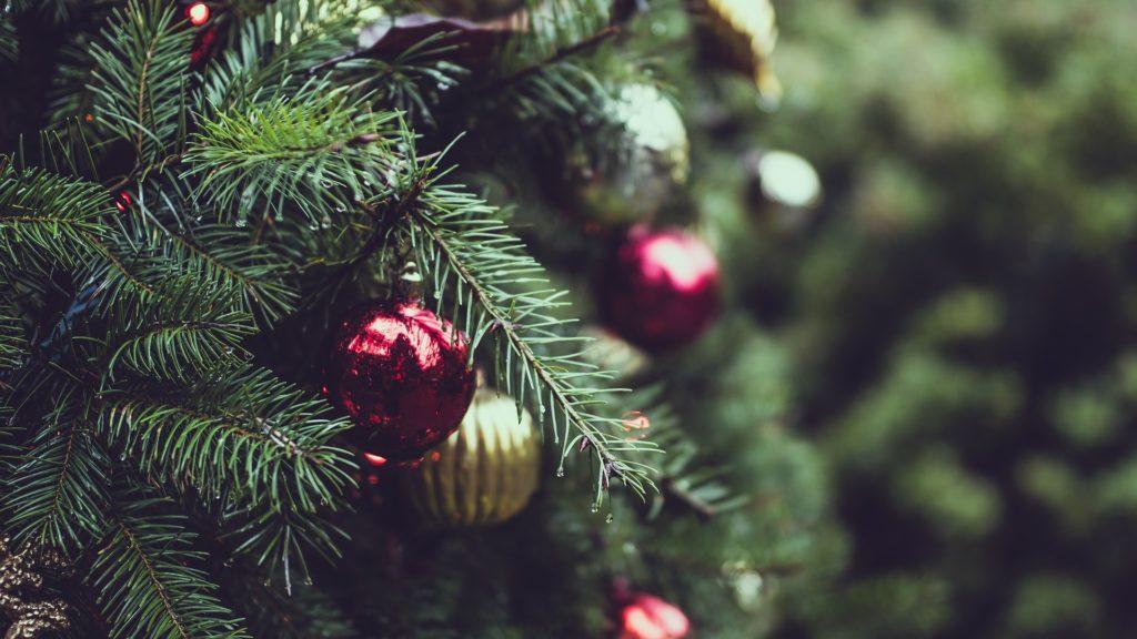Un primo piano di un albero di natale con delle palline rosse e dorate in mezzo ai rami verdi