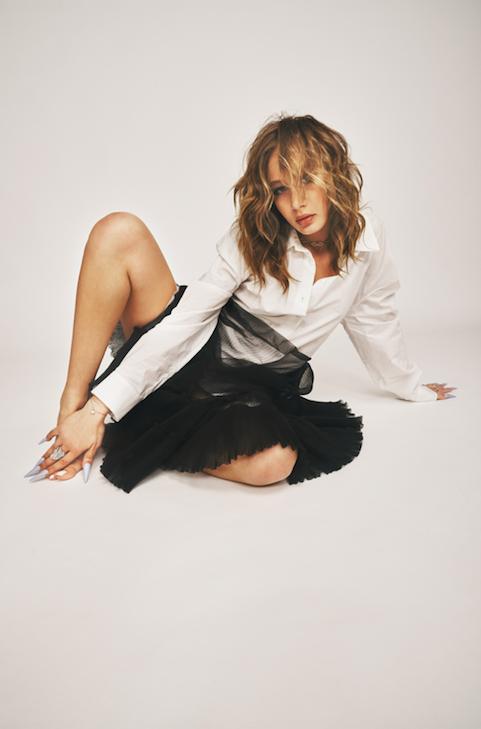 In foto la rapper Chadia Rodriguez, indossa una camicia bianca, una gonna di tulle nera, appoggia una mano dietro di sì e con l'altra si tocca il piede, è seduta per terra su uno sfondo completamente bianco e guarda davanti a sé