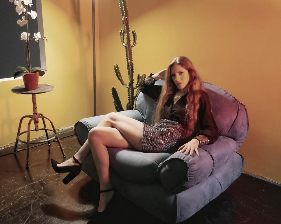 Ilaria Di Nino seduta su una poltrona di pelle, le gambe accavallate, minigonna e camicetta nera