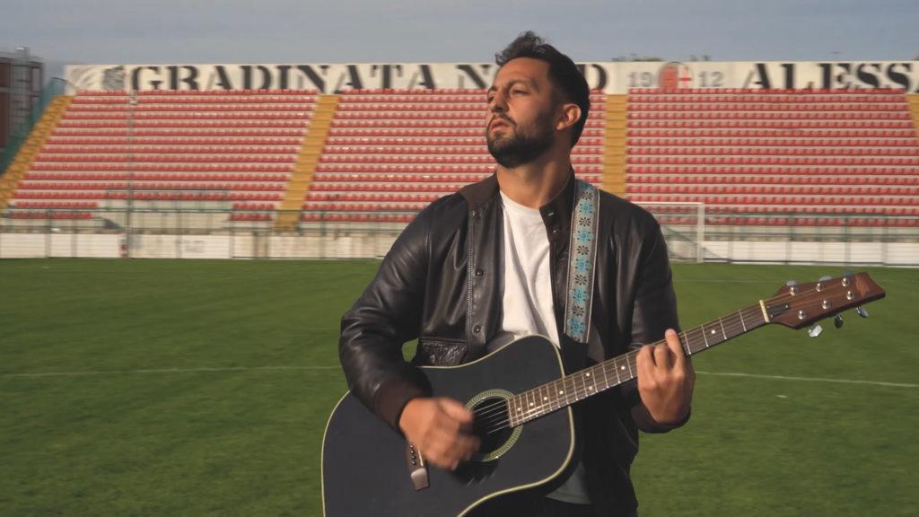 il discorso del capitano - leone, t-shirt bianca e giacca di pelle, chitarra nera a tracolle. sullo sfondo la gradinata dello stadio moccagatta di alessandria