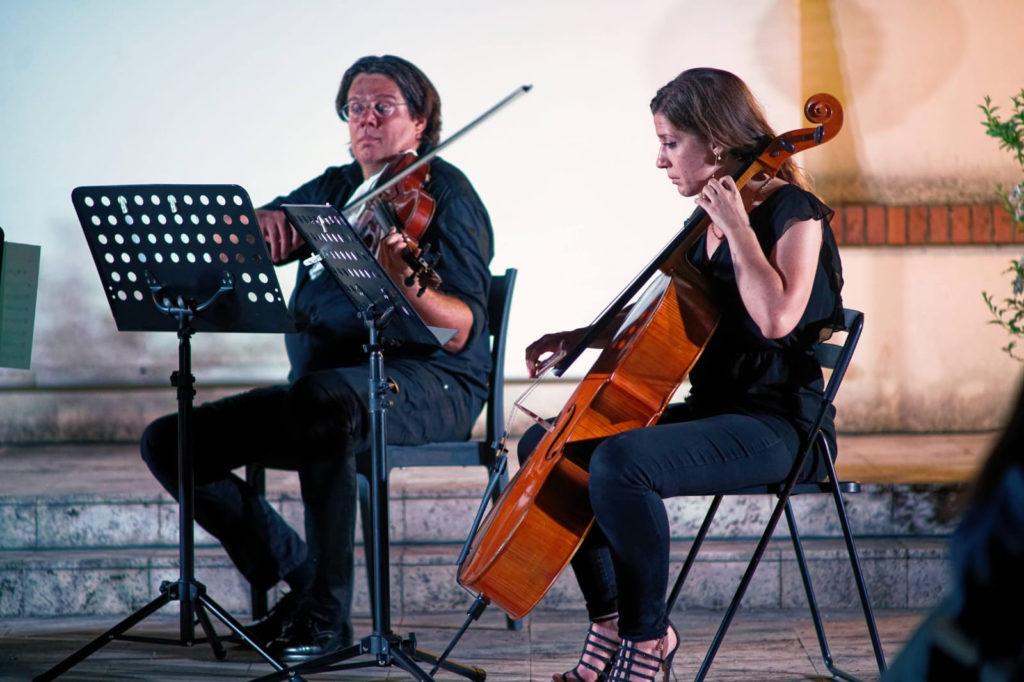 Morian Taddei e Orchesta Italiana del Cinema mentre suona il violino e vicino a lui una musicista con un violoncello