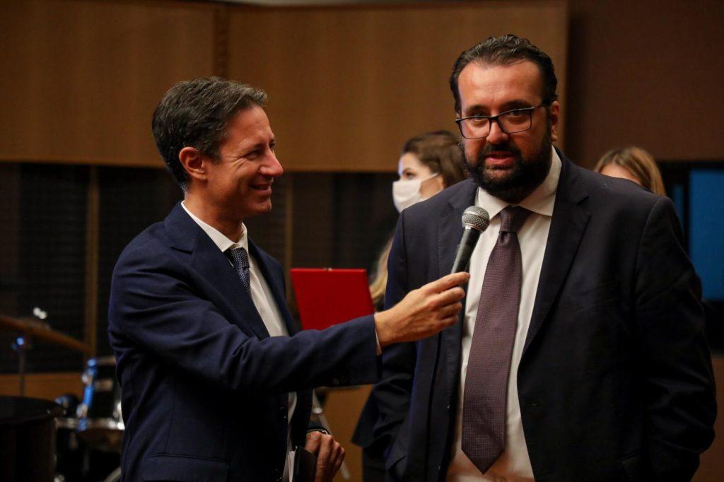 Roma Music Festival casting - sulla sinistra Stefano Raucci vestito elegante tiene in mano il microfono per far parlare Andrea Montemurro, con barba e occhiali, giacca e cravatta rossa