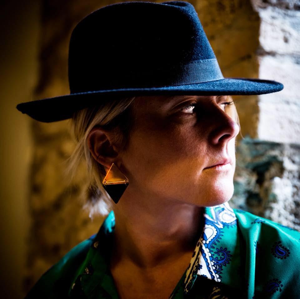 eugenia martino di profilo orecchini a triangolo, cappello nero in testa