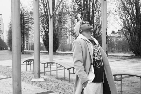 In foto il rapper tre, la foto è in bianco e nero, lui è in un parco, indossa una cuffia, gli occhiali da sole, un cappotto, maglia nera dei Queen, felpa e pantalone bianchi. Ha la mano in tasca e guarda verso l'alto