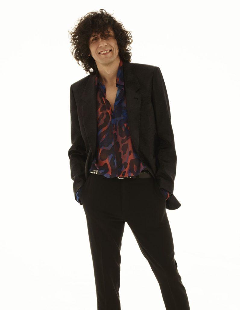In foto Ermal Meta, vestito di nero, con una camicia a fantasia rossa e blu, sorride davanti all'obiettivo, è in piedi e tiene le mani in tasca, lo sfondo è bianco