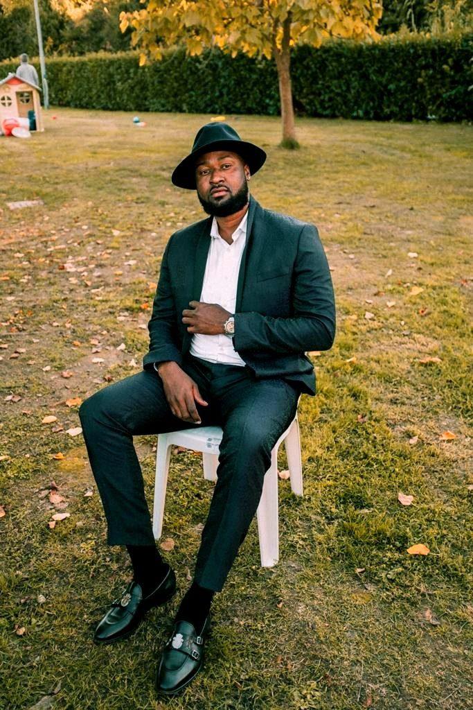 Charles Onyeabor seduto su una sedia di plastica bianca, che indossa un vestito blu, cappello  e camicia bianca