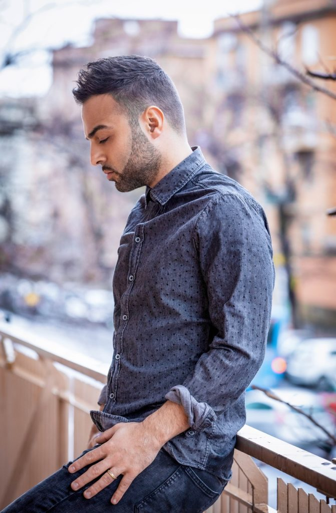 giuseppe salsetta appoggiato a una ringhiera, sullo sfondo un panorama cittadino, indossa jeans e camicia blu