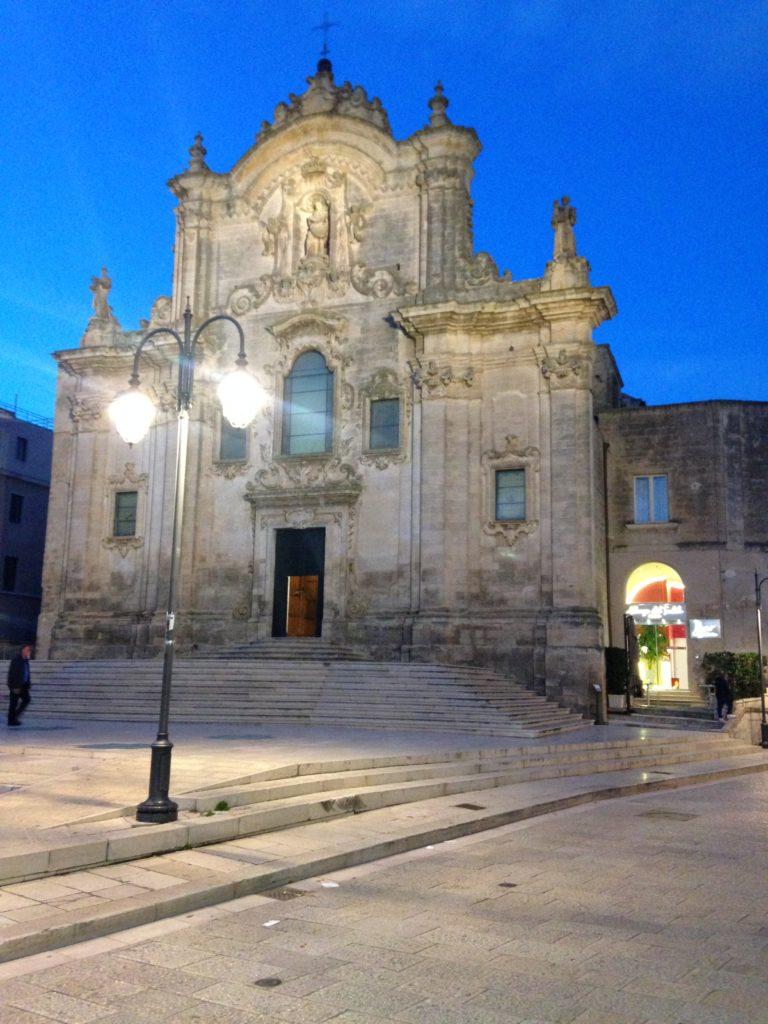 la facciata di una chiesa di matera, veduta di notte con un lampione acceso nella piazza antistante