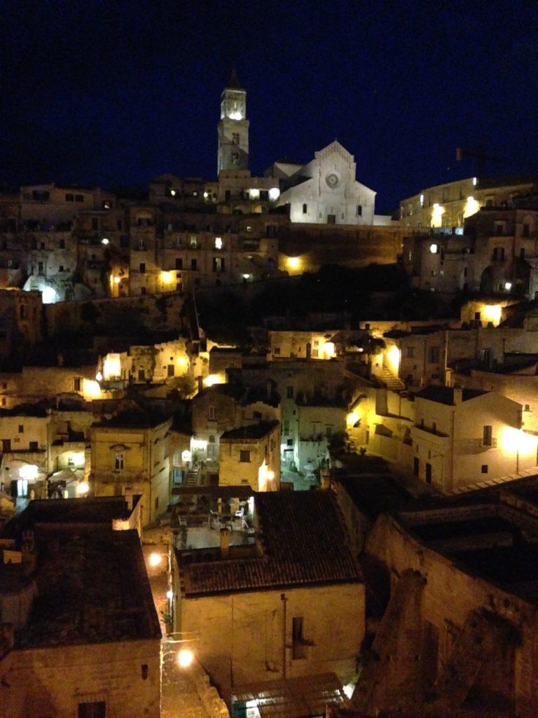 veduta panoramica di Matera di notte con le luci delle case accese, sembra un presepe