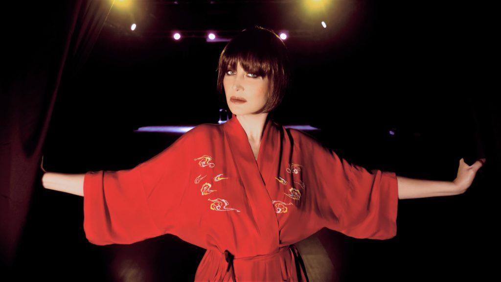 valentina mattarozzi nostalgie - la cantante, a braccia aperte, indossa una vestaglia rossa in stile giapponese