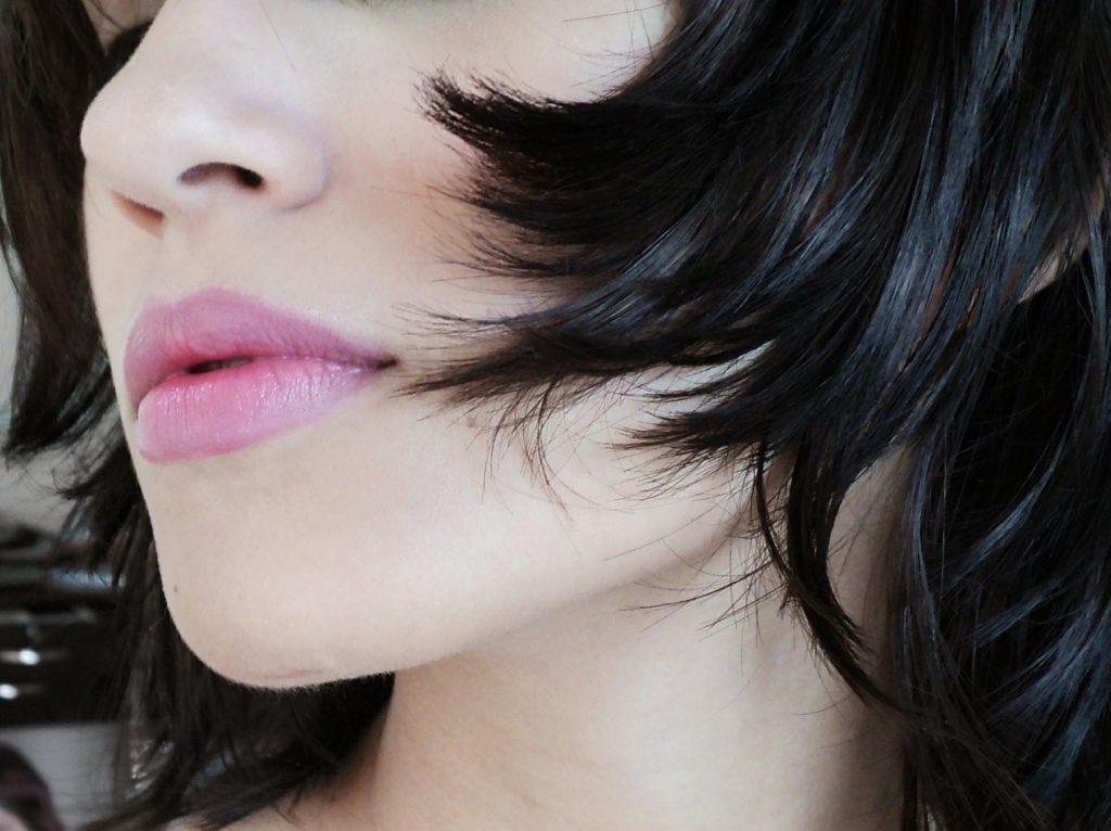 il primo piano di mezzo volto di una donna con una pelle luminosa, labbra carnose rosa e capelli a caschetto che cadono sulle guance