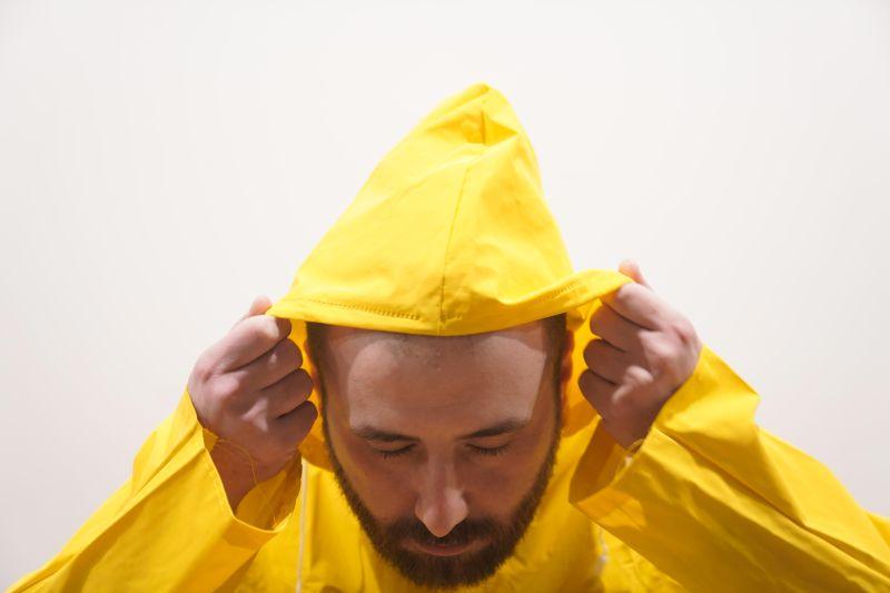luvespone pioggia su di me - il cantautore con un impermeabile giallo, intento a tirare il cappuccio sulla testa
