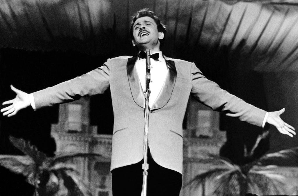 Domenico Modugno in una foto in bianco e nero con le braccia aperte canta davanti a un microfono. Infdossa giacca chiara con colletto nero