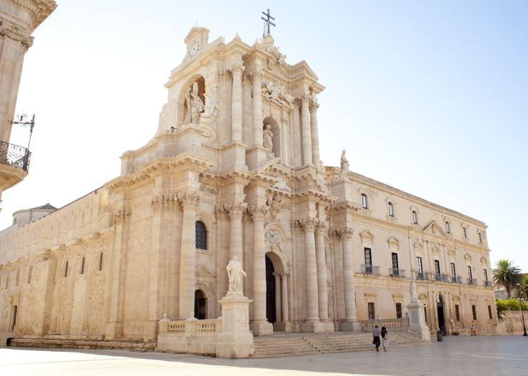 Siracusa, il duomo, con un'alta torre all'angolo, la facciata è chiara ed è adornata di colonne. ai lati della scalinata centrale si ergono due statue
